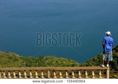 man overlooking Laguna de Apoyo Nature Reserve Nicaragua