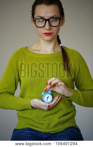 Little blue alarm clock in the hands of pensive young woman concept of saving time