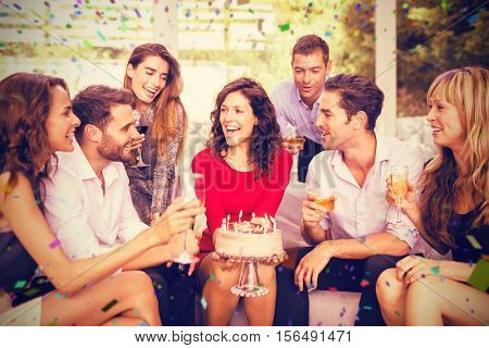 Cheerful woman celebrating her birthday with friends against flying colours