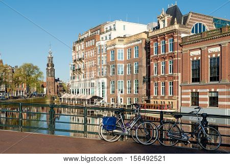 Bikes on the bridge with Netherlands traditional houses and Amsterdam canal in Amsterdam Netherlands.
