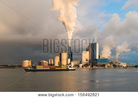 Smoke of heavy industry is highlighted by the sun. Shot in the Netherlands industry area of the Europoort in Rotterdam Netherlands