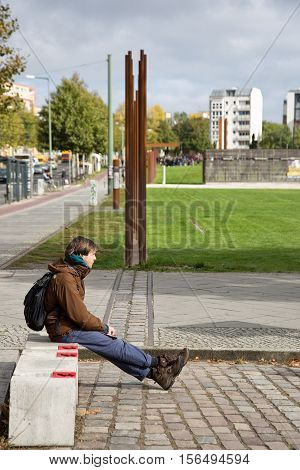 Berlin Germany - October 07 2016: Man sits on the east and west side of where the old Berlin Wall stood in Berlin Germany