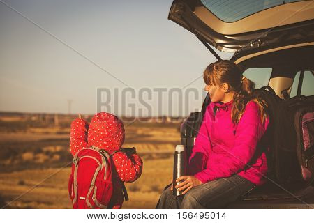 mother and little daughter travel by car in scenic mountains