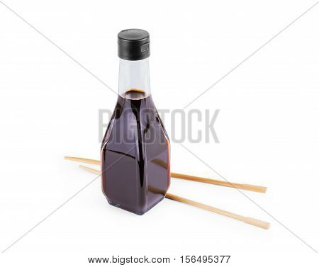 splashes of soy sauce and chopsticks isolated on white. wooden chopsticks dipped in soy sauce spilled.