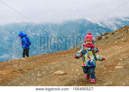 family winter travel - little girl and boy hiking in winter mountains