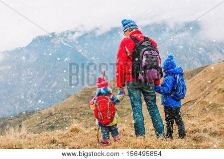 father with two kids travel in scenic winter mountains