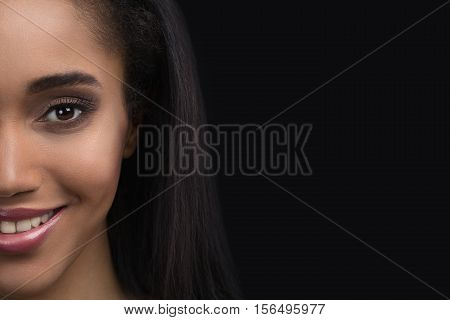 Half-face portrait of beautiful smiling sensitive afro american woman on dark background.