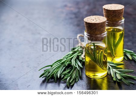 Healthy lifestyle concept. Natural rosemary essential oil on a rusty black table for beauty, spa, therapy. Selective focus, copy space background
