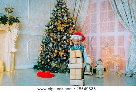 little boy with christmas presents in decorated living room, christmas celebration