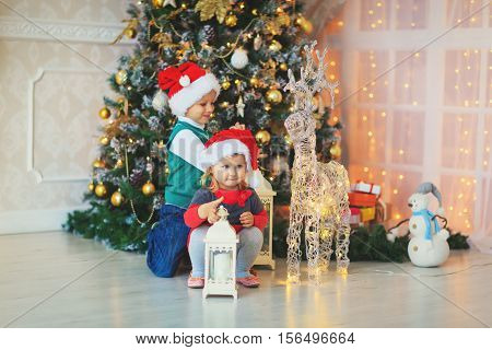 cute little boy and girl waiting for presents in decorated living room