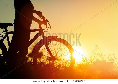 silhouette of young woman riding bike at sunset nature