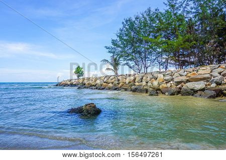 Stone embankment near sea shore with tropical tree in Labuan Pearl Of Borneo, Malaysia. Stone embankment to prevent the waves of the sea also ensure watertightness, support, stabilization.