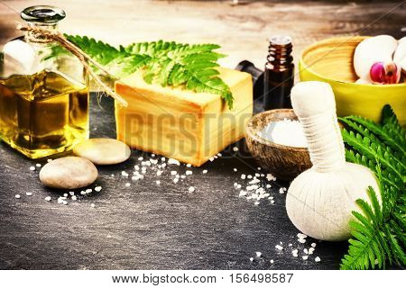 Spa setting with herbal massage ball flowers and essential oil. Wellness and beauty concept