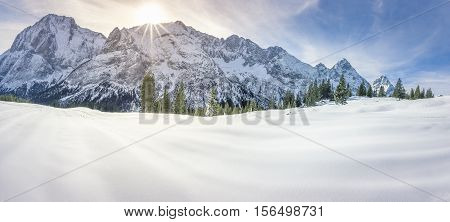 Snowy mountains and valley - Dreamy winter panorama with the Austrian Alps mountains the fir forests and a thick layer of snow over a valley on a sunny day of December.