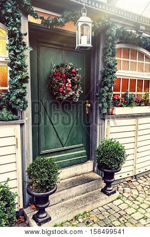 Christmas house decoration with fir wreath on the door. Christmas concept in retro style