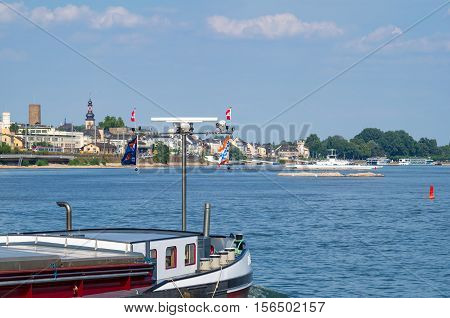 Ruedesheim am Rhein seen from the Rhine River with the landing place and a barge in the foreground