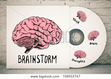 Close up of CD cover with creative human brain sketch on brick background. Brainstorm concept. 3D Rendering