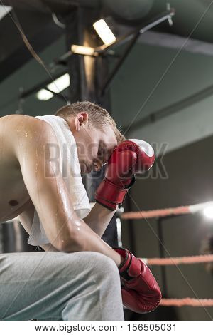 Tired boxer wearing boxing gloves sitting on a ring during training