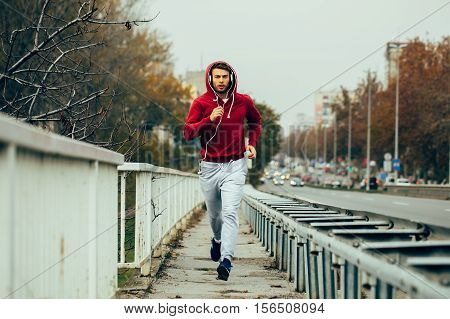 Man in red hoodie jogging beside the road in the city