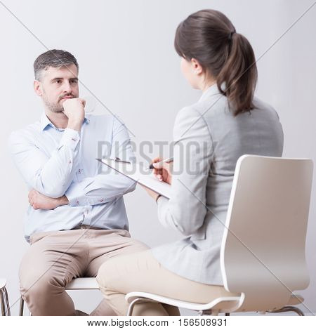Young man and woman sitting on a group psychotherapy