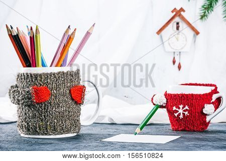 Big and little mugs in wool warmers holding color pencils