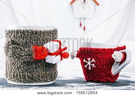 Big mom mug in wool warmer giving the gift box to little kid cup