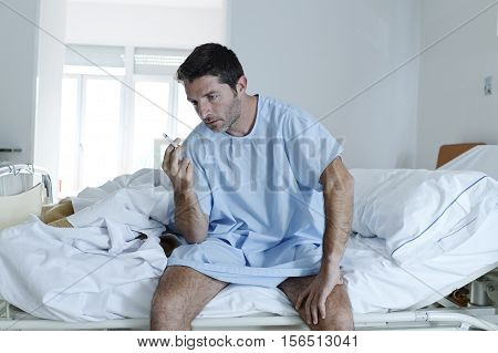 young attractive man looking sad and worried at hospital bed smoking cigarette in clinic bedroom looking defiant in lung cancer diagnose and anti tobacco advertising campaign concept