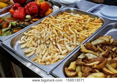 Steel container with roasted potato wedges, country stile potatoes