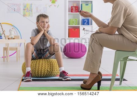 Boy Sitting On A Pouf, Talking With A Psychotherapist