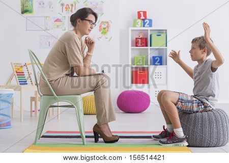 Angry Young Boy Sitting On A Pouf