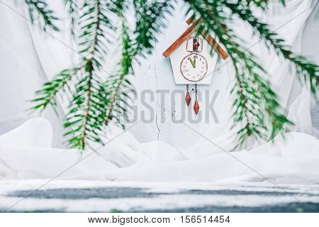 Handmade toy cuckoo clock on the white wall through evergreen branches. Concept of christmas advent. Selective focus