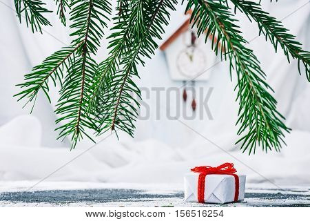 Gift box under evergreen branches with handmade toy cuckoo clock on the white wall on the background. Concept of christmas advent