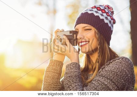 Modern millennial female photographer outdoors taking a photo using analogue camera. Beautiful young woman in autumn photographing something using film camera, smiling. Retouched, back lit.