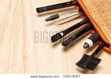 Accessories for care of brows and lashes. Brow comb, eyebrow pencil, angled brushes, tweezers, spoolie brush in cosmetic bag on wooden background. Eyebrow and eyelash grooming tools. Copy space poster