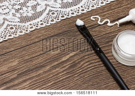 Beauty products for skin around the eyes. Eye cream squeezed out of tube, glass jar of gel for eyelids, applying brush with sample on wooden surface with white lace. Copy space. Shallow depth of field