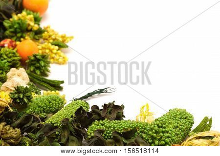 Variegated corner frame of dried herbs, plants and flowers on white. Beautiful natural background. Shallow depth of field