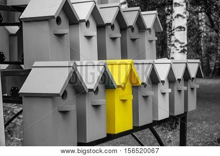 Yellow color wooden birdhouse stand out from the crowd. Metaphor to business concept. Stands out among the gray of similar objects. Notable among the competitors.