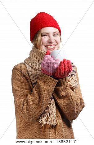 Young smiling woman in brown sweater buff scarf red cap and gloves standing with cup isolated on white background
