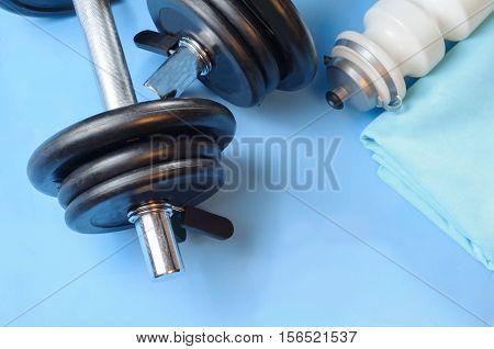 Sport items - dumbells, sport bottle, sport towel - on the sport mat