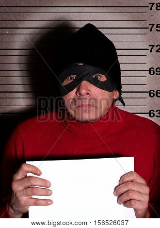 Angry burglar in a red sweater black hat and mask holding a white poster with empty space for text while standing against police line-up