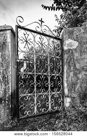 Old metal fence gate with cross in black and white