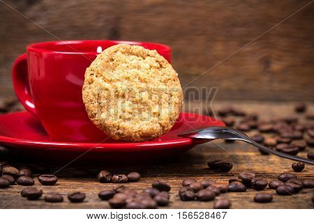 Coffee cup with biscuit and coffeebeans on dark wooden table