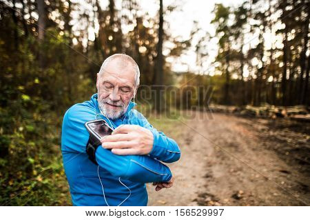 Senior runner in nature. Man with smartphone and earphones, adjusting settings on armband for phone. Listening music or using a fitness app. Using phone app for tracking weight loss progress, running goal or summary of his run. poster