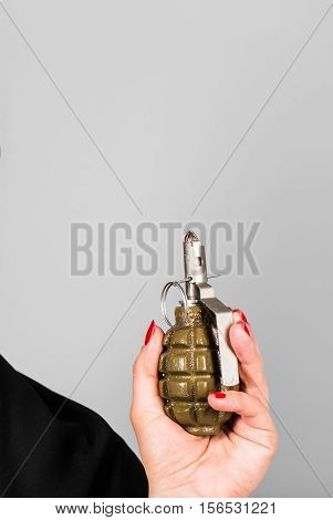 Woman's hand with grenade. Concept of war