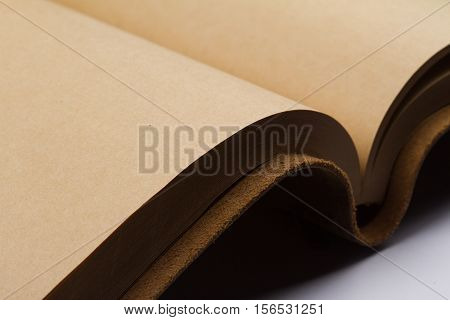 close up of empty pages of a leather covered book binding