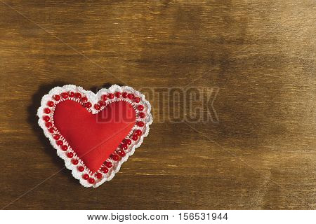 Valentine's Day background. Handwork red heart on the wooden background with place for text