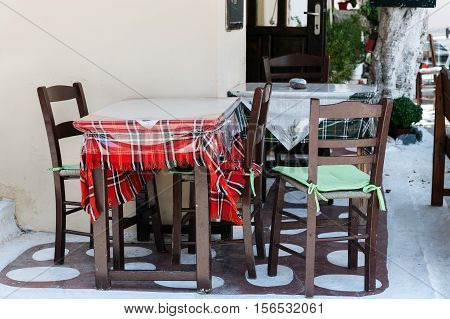 Wooden table with chairs at traditional Greek cafe