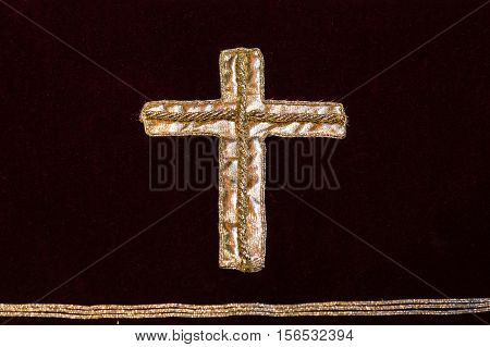 A gold cross embroidered on a dark red cloth