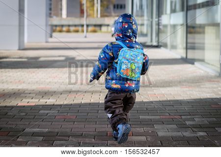 RIGA, LATVIA - NOVEMBER 2016: Little boy with rucksack is  running on a street