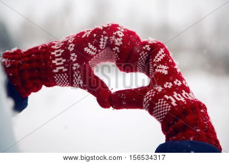 hands in red mittens folded heart in snow winter